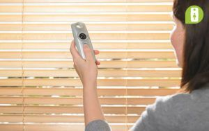 Woman opening her blinds using a Somfy remote control