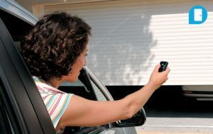 Woman in her car using a Somfy smart key to remotely open her garage door