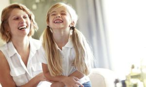 Woman and daughter laughing on sofa