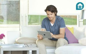 Man sitting on a sofa using his Tahoma smart home app