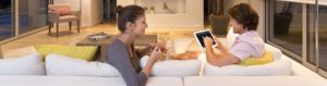 Couple sitting on their Somfy and adjusting their lights using Somfy Tahoma iPad app